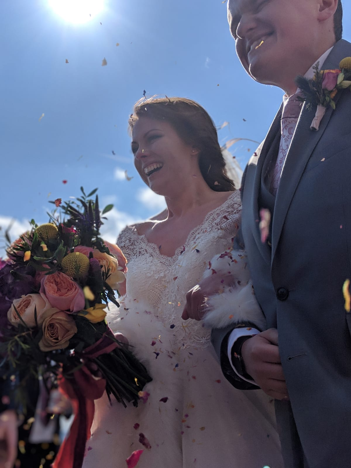 Happy couple after church ceremony with bright bouquet and confetti