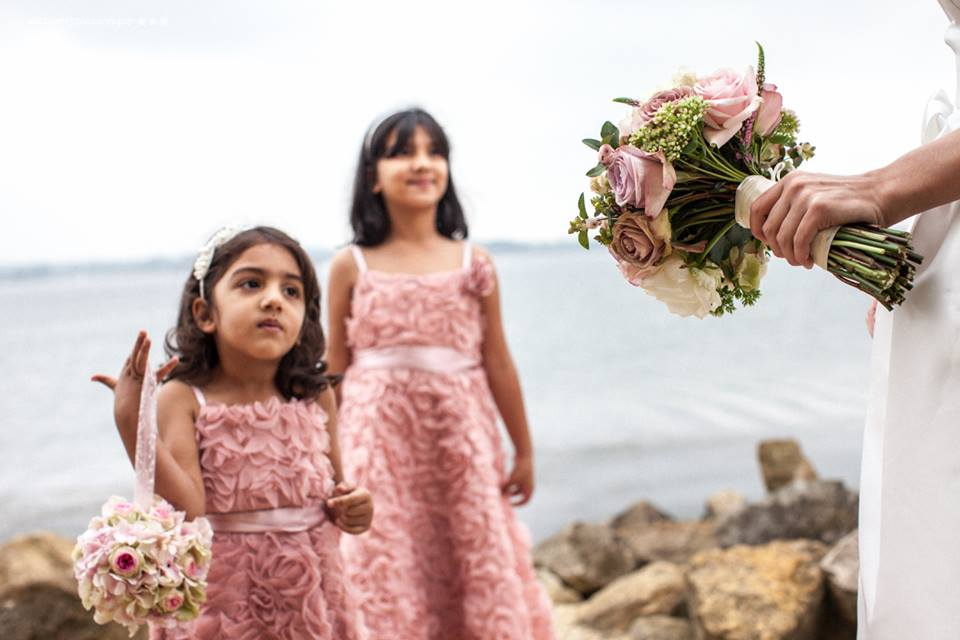 Bride with flower girls holding their flowers. blush and dusky pinks