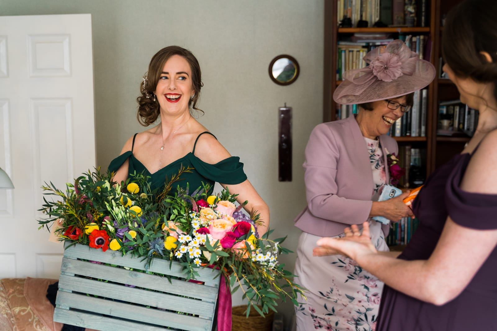 Happy bridesmaid holding a crate full of flowers