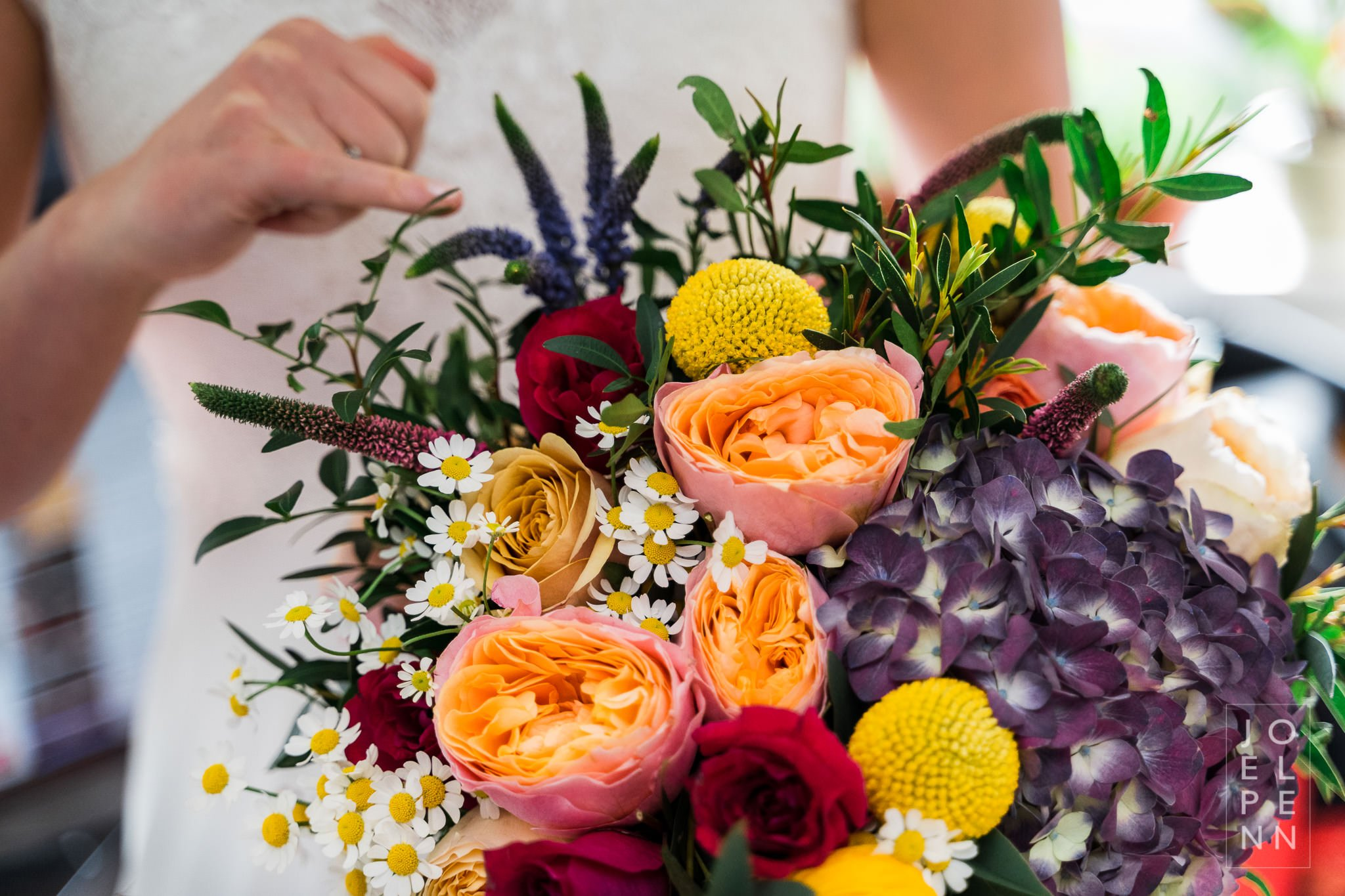 Bride pointing at her bridal bouquet of bright vibrant flowers