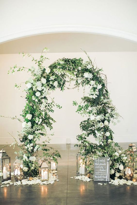 Large wispy summer floral arch with white flowers, lanterns and candles