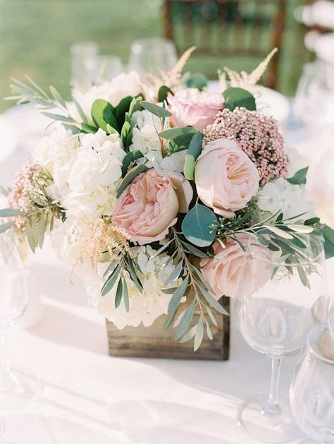 Summer table arrangement in a wooden box with peonies and roses