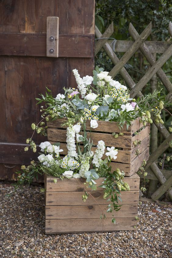 two wooden crates filled with beautiful green and white flowers from summer