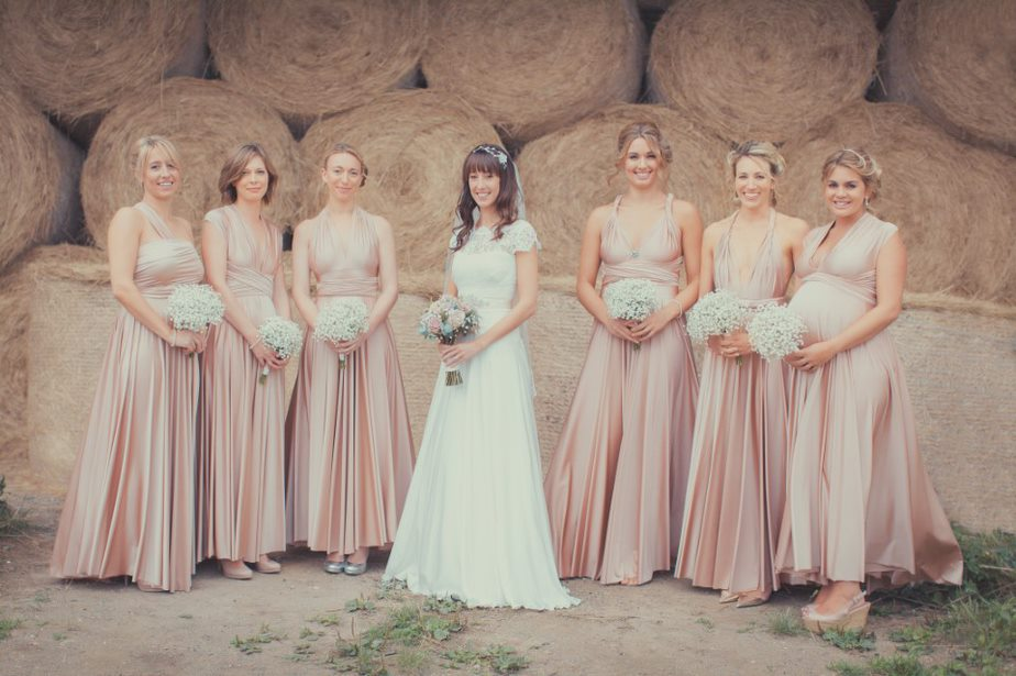 Brides with her bridesmaids against a rustic backdrop blush pinks