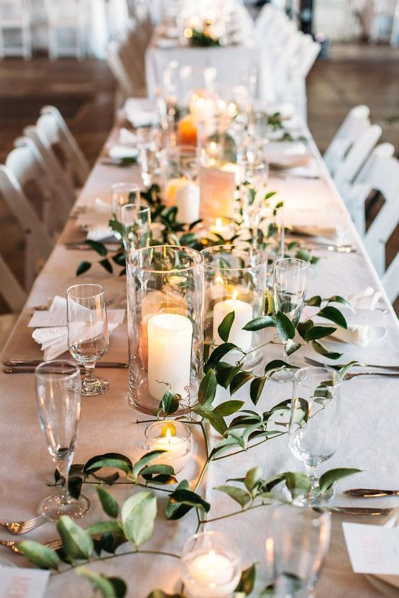 Simple elegant wedding table setting with olive springs and candles