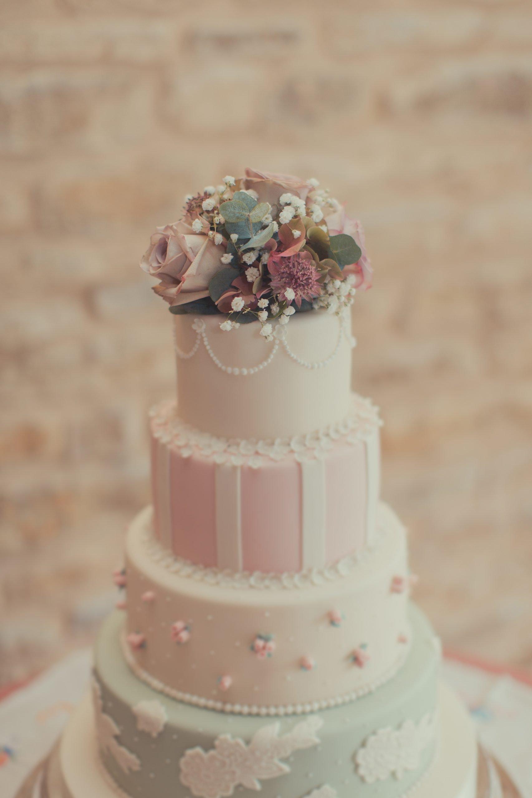 Wedding cake with vintage flower arrangement on top.dusky pinks