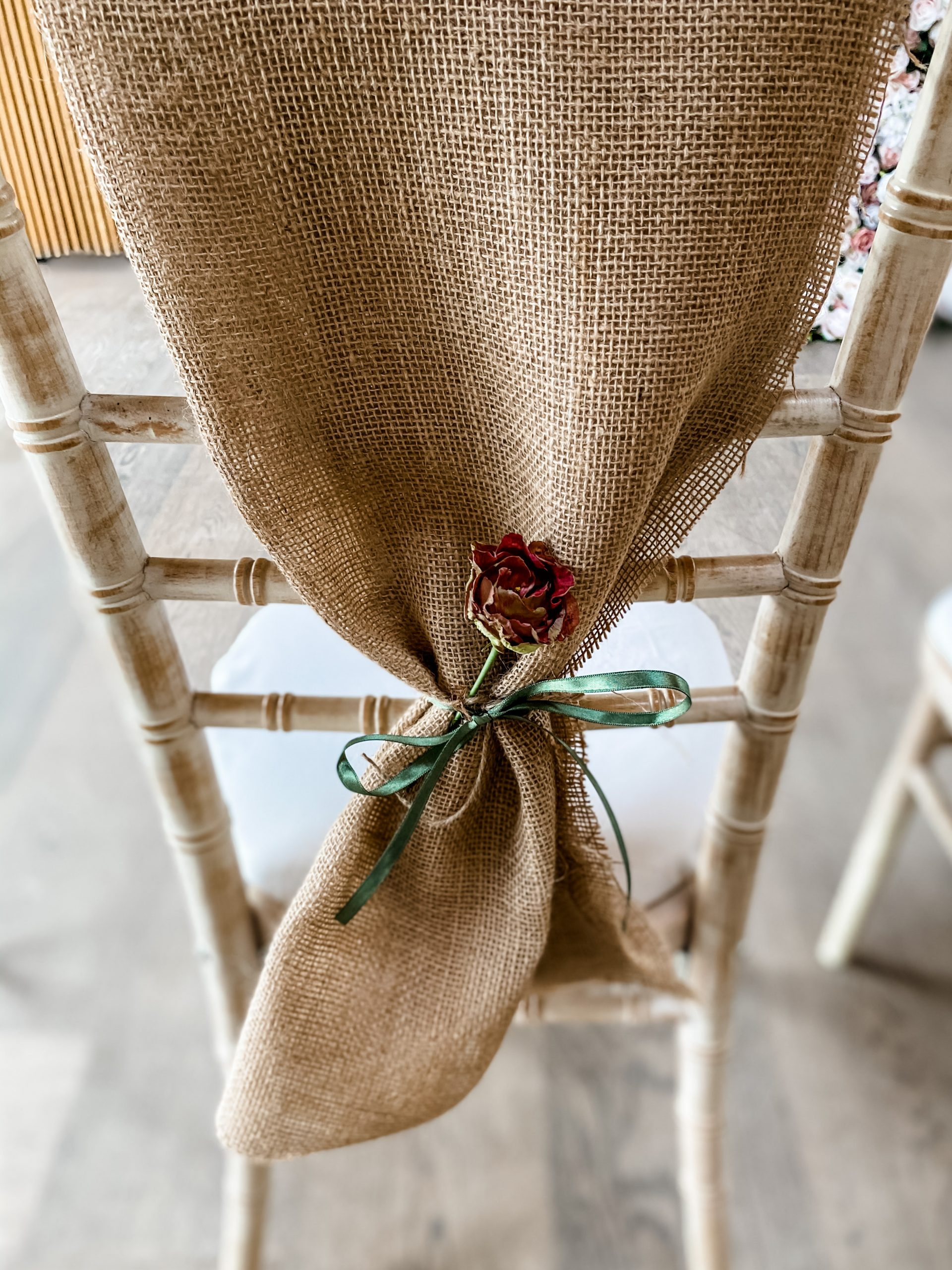Hessian chair back for wedding or event, with a sprig of flower and silk ribbon