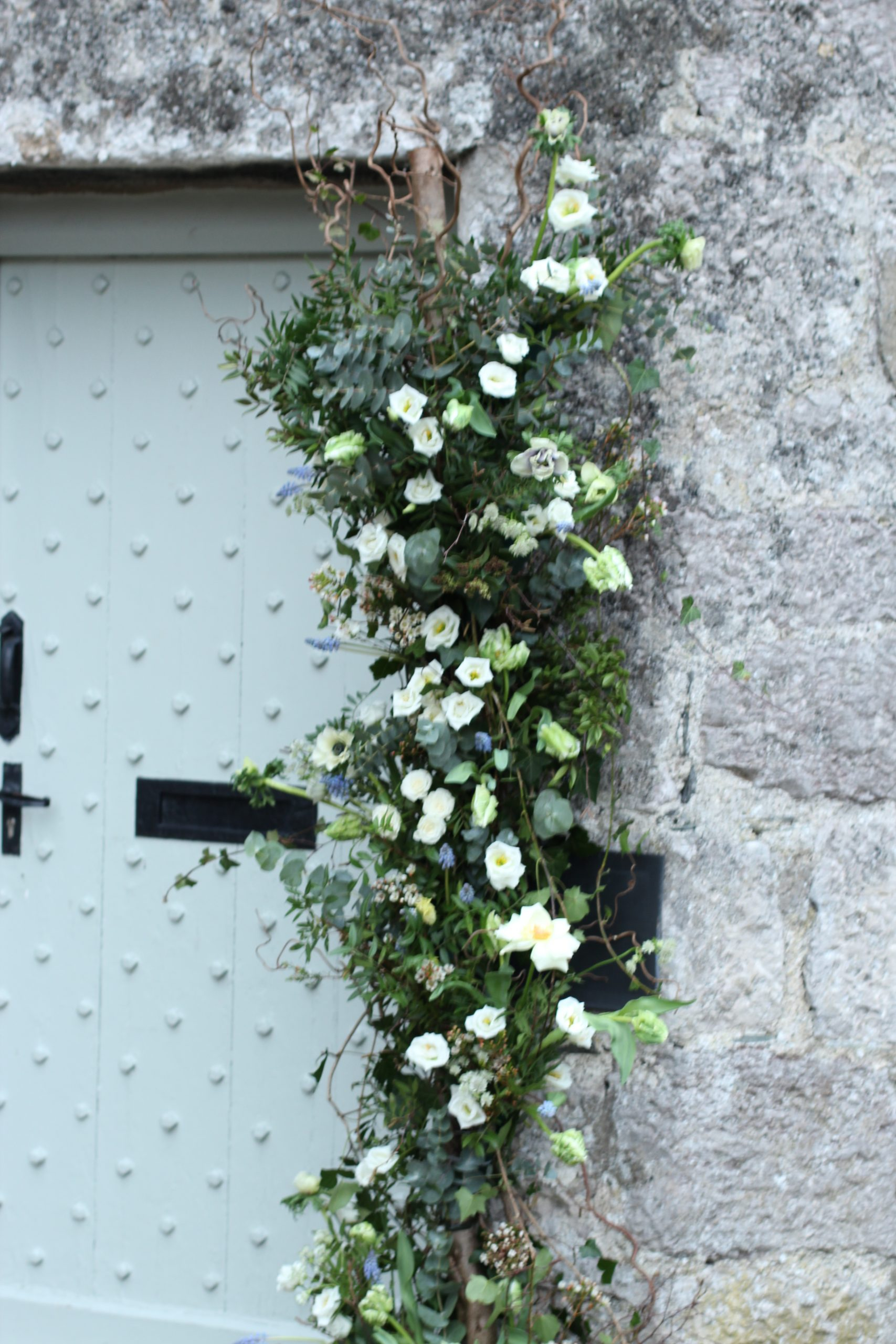Spring flower arch against stone wall. Green and white tones