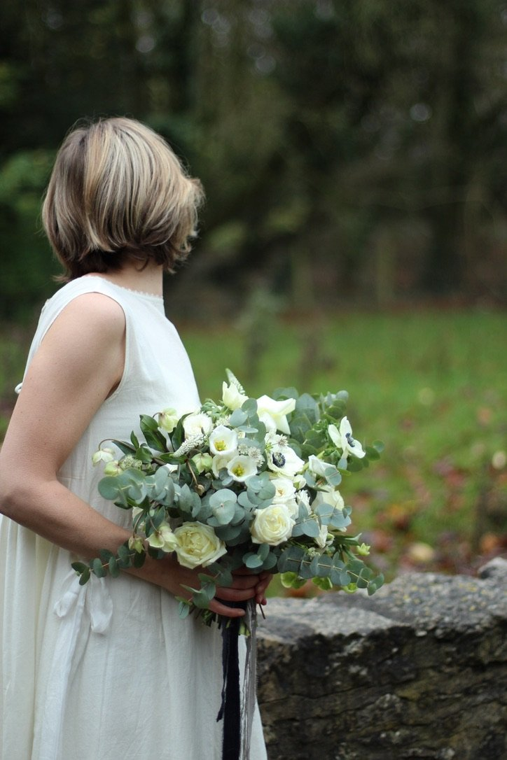 Bride with bouquet of green and white, anemone