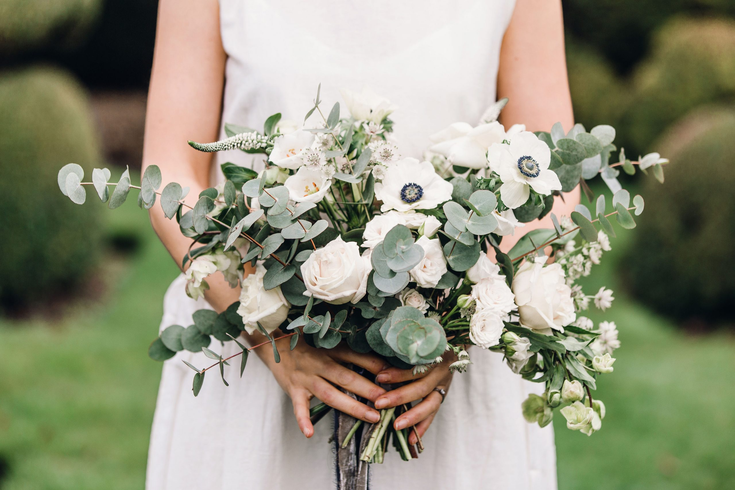 Bride holding bridal bouquet, natural and relaxed.