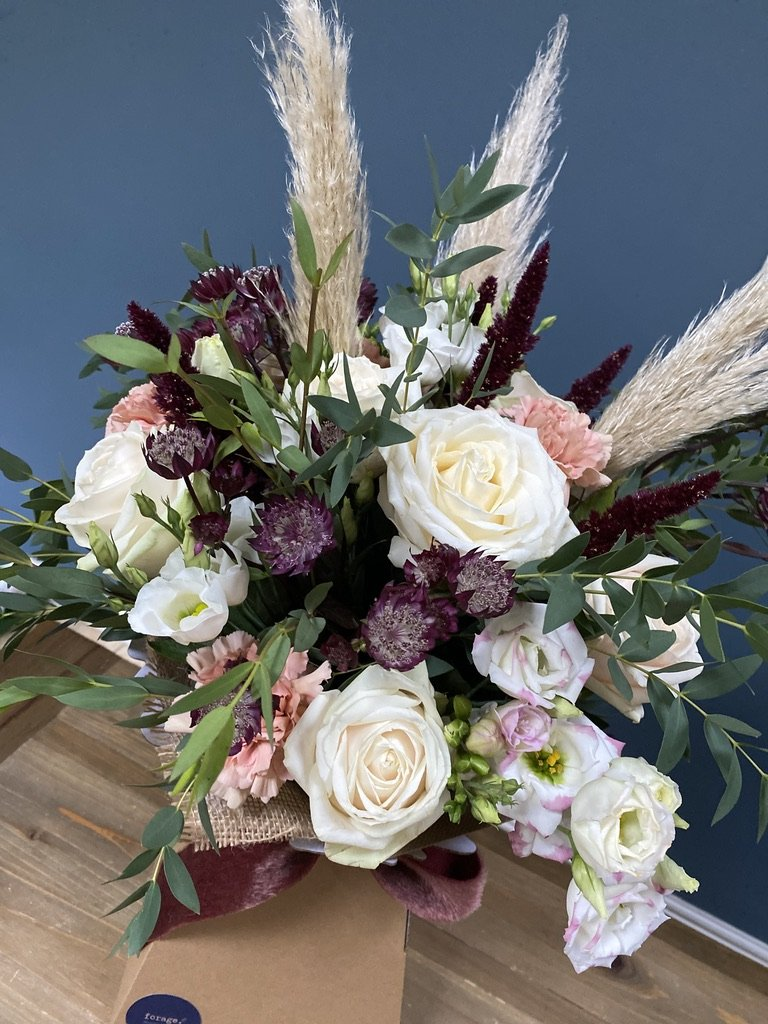 Luxury gift bouquet wrapped in material and in a gift box