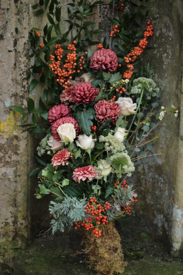 Eco friendly funeral spray with seasonal blooms and ilex berries