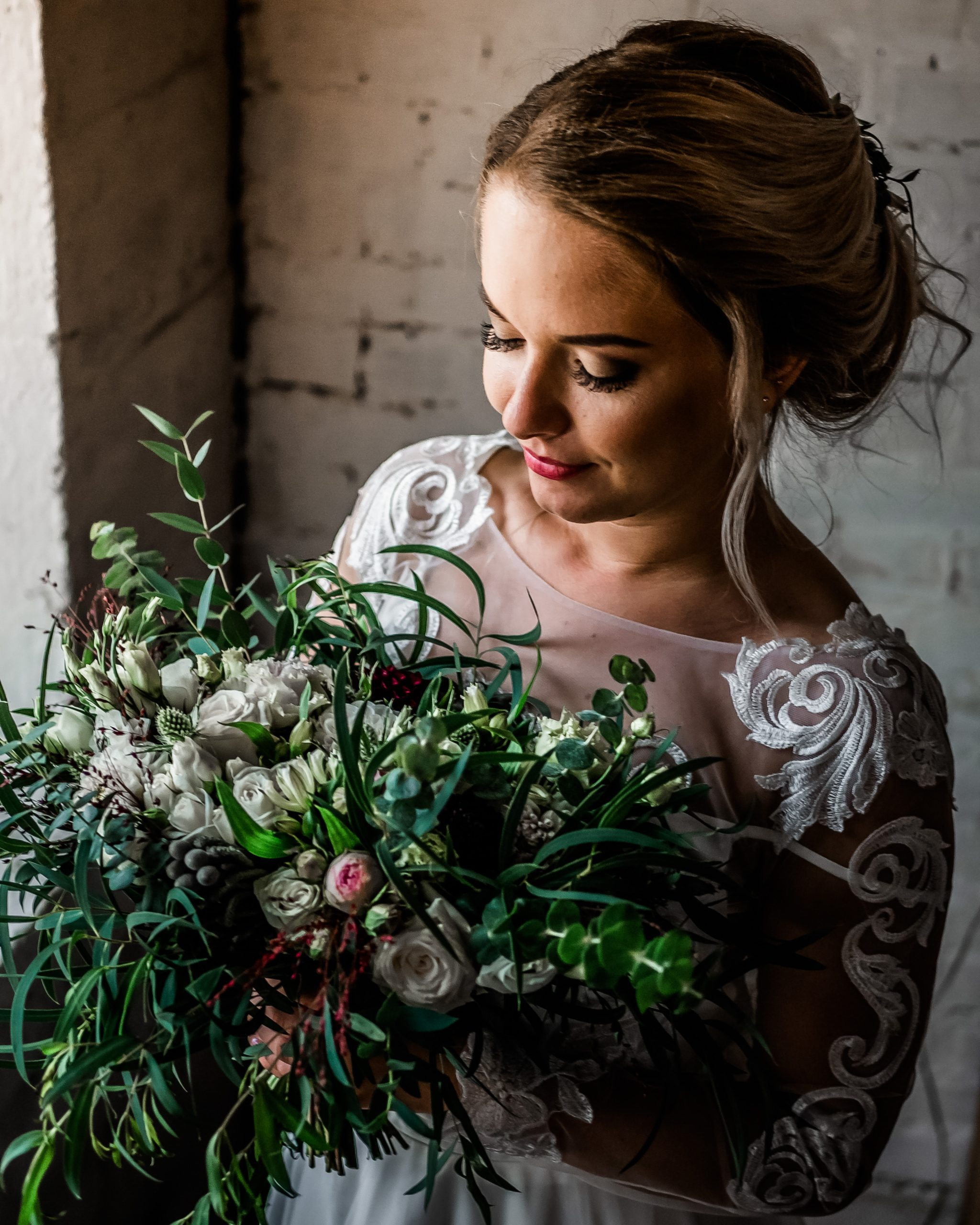 Bride standing at a window admiring her bouquet